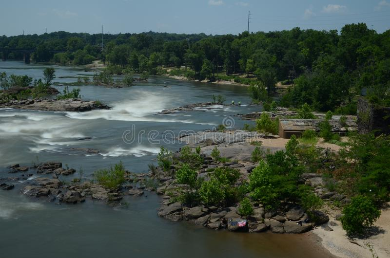 River rapids in motion with woods and green around it royalty free stock photo