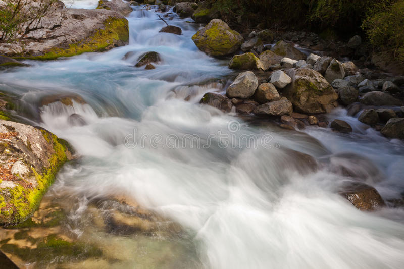 River rapids washing over rocks with silky look. Small natural river casdcading over rocks with silky appearance from long exposure royalty free stock photos