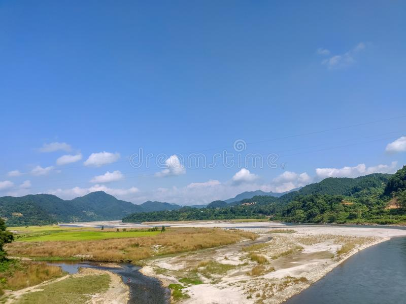 River, river bank, farm land and hills in Nepal.  royalty free stock photos