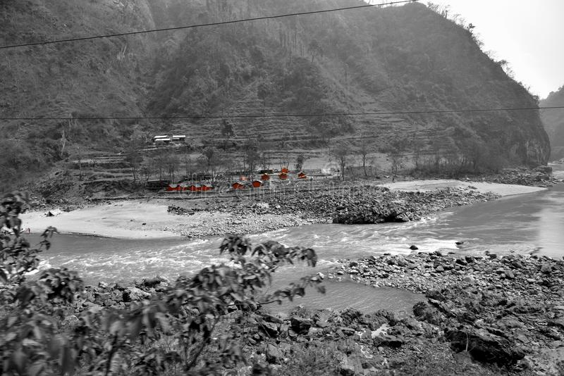 River and road to Chitwan in Nepal. A green river snaking among the mountains great views, climbing to small mountains, white photo with an accent of red stock photography
