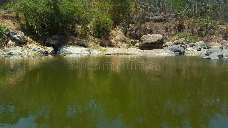River with rock cliffs and clear water. Seemed to dry up due to long drought stock photography