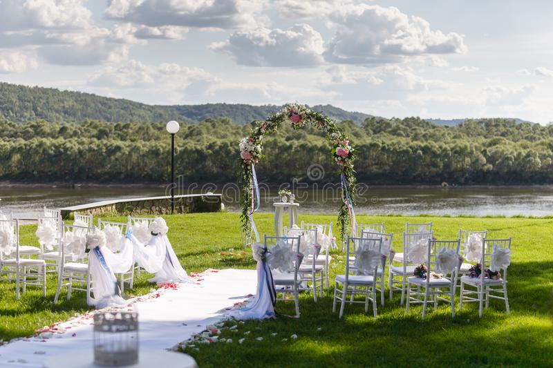 river romantic wedding ceremony white wooden chairs with ribbon