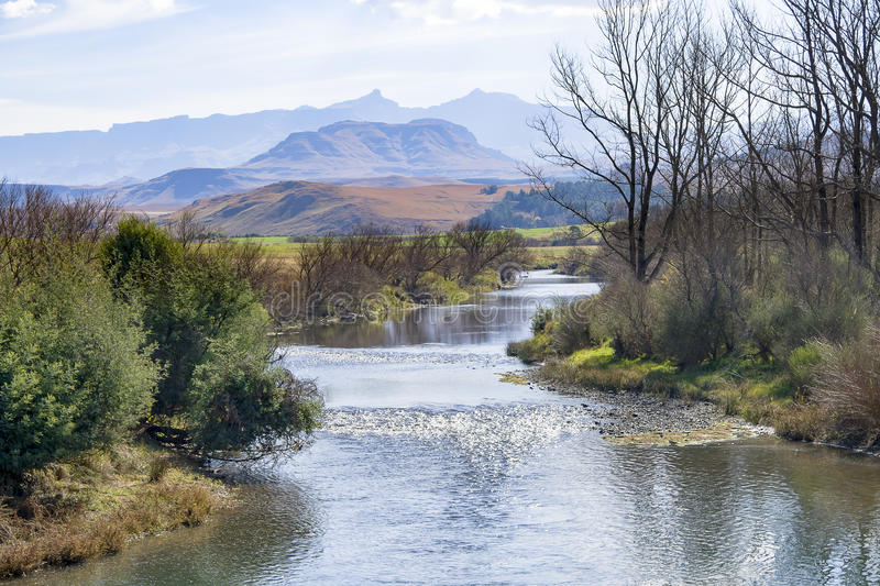 A river runs through the foothills of the Drakensberg Mountain Range at Underberg in South Africa. The Underberg region covers an area from foothills to some of stock photos