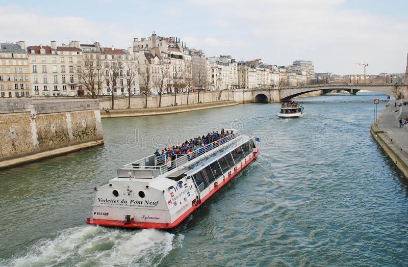 River Seine excursion boats, Paris. Excursion boats head towards the Pont De La Tournelle on the River Seine in Paris, France on March 18, 2014. Numerous boats royalty free stock photography