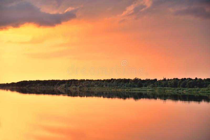River, sky, clouds before the rain, summer sunlight, reflections of trees and sky in water, red-yellow sunset stock photo