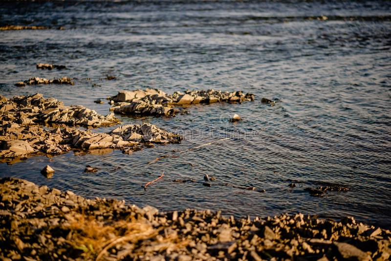 Quiet river water in the evening light background. River stones, Pebble river banks.great for gaming background, shot in warm evening light stock image