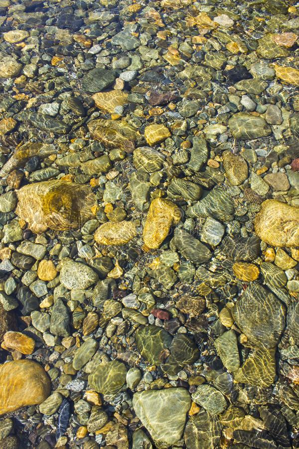 River Stones in Shallow Water. Stones under the surface of a shallow ,crystal clear, mountain river stock photography