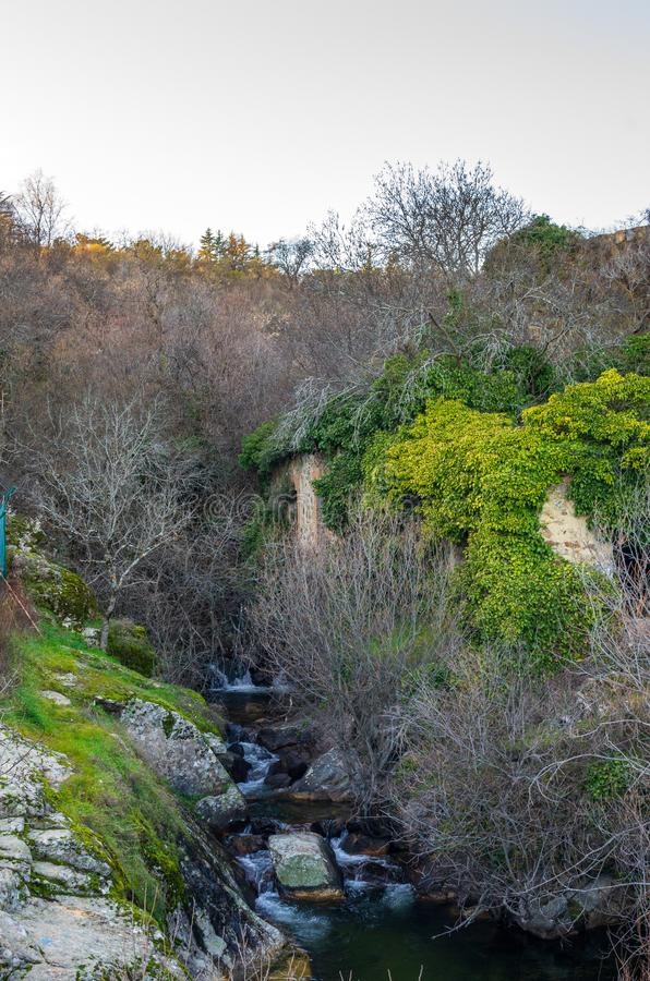 River stream flowing between the rocks next to the ruins of an old mill. River stream flowing between the rocks next to the ruins of an old water mill in spring royalty free stock photos