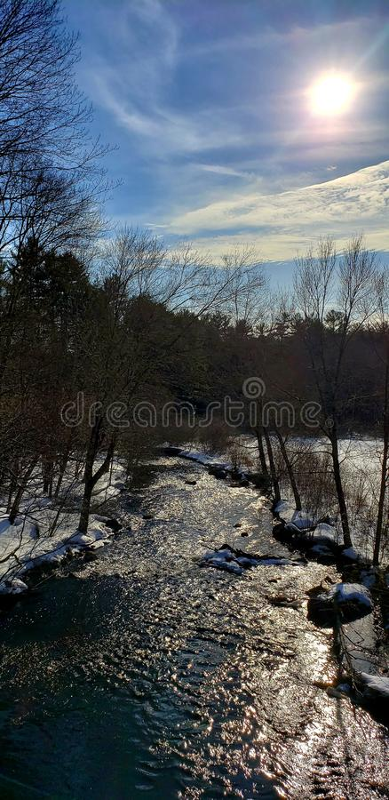 River and Streams. River streams winter outdoors hiking sunburst sky clouds snow royalty free stock photos