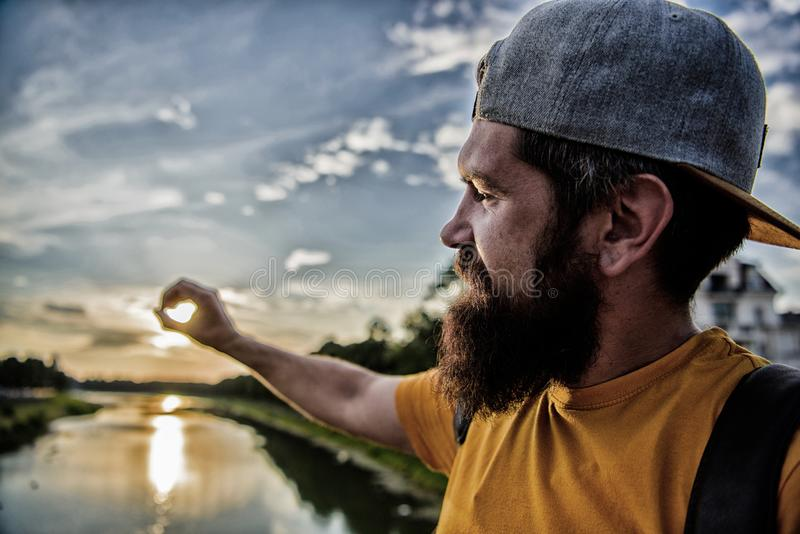 River sun reflection. Enjoy pleasant moment. Guy in front of blue sky at evening time admire landscape. Take moment to. Admire sunset nature beauty. Man in cap stock photography