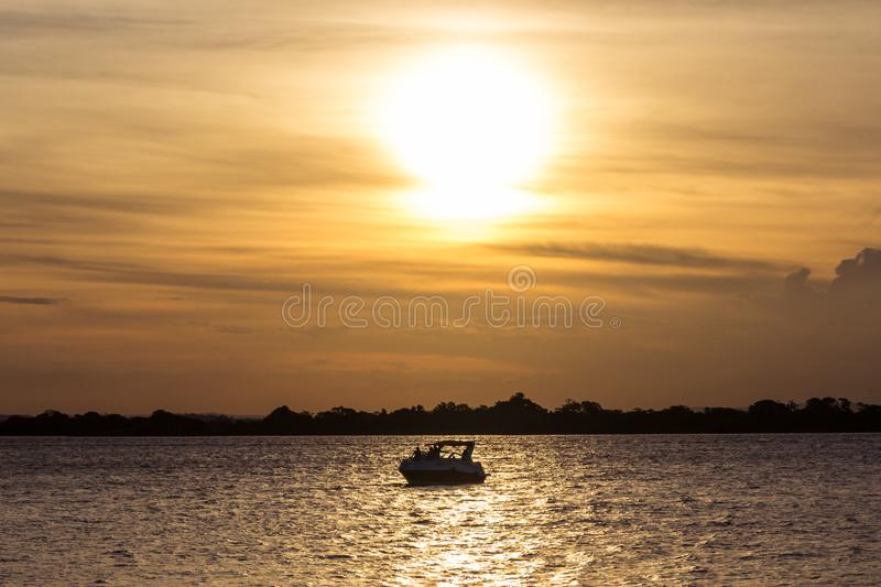 A river at sunset with a boat. This in one of the best sunsets in brazil. This is the city of Porto Alegre with one boat in the river royalty free stock photography