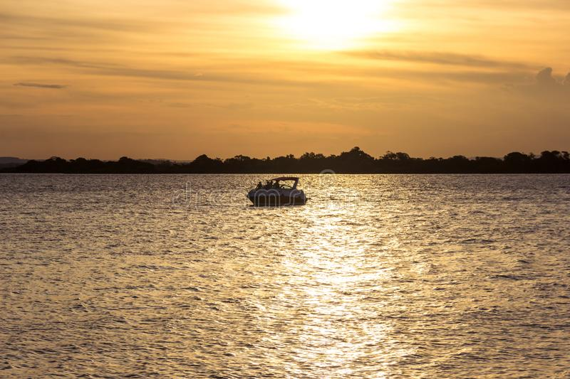A river at sunset with a boat. This in one of the best sunsets in brazil. This is the city of Porto Alegre with one boat in the river stock image