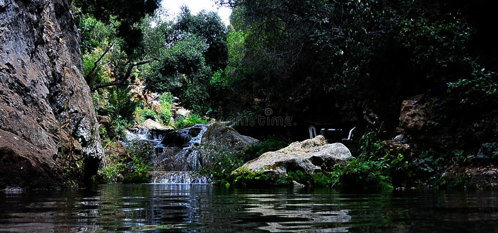 River Surrounded by Rocks and Trees royalty free stock images
