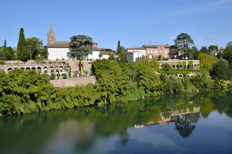 River Tarn in the village of Lisle-sur-Tarn in France. River Tarn in the village of Lisle-sur-Tarn with the church and arcades in the background, commune in the stock image