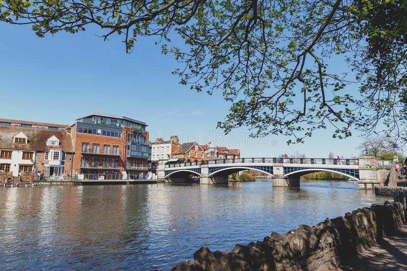 The River Thames flowing through Windsor and Eton, twin towns in Berkshire, joined by Windsor Bridge, England UK. Berkshire, UK - April 2018: The River Thames royalty free stock photo