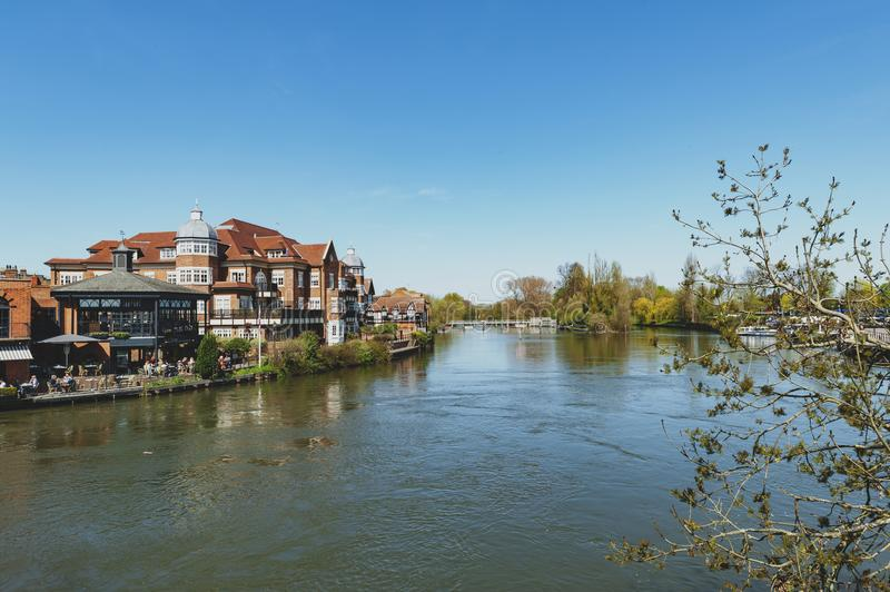 The River Thames flowing through Windsor and Eton, twin towns in Berkshire, joined by Windsor Bridge, England UK. Berkshire, UK - April 2018: The River Thames stock photography