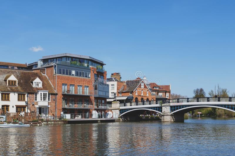 The River Thames flowing through Windsor and Eton, twin towns in Berkshire, joined by Windsor Bridge, England UK. Berkshire, UK - April 2018: The River Thames royalty free stock images