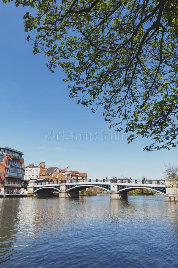 The River Thames flowing through Windsor and Eton, twin towns in Berkshire, joined by Windsor Bridge, England UK. Berkshire, UK - April 2018: The River Thames stock image