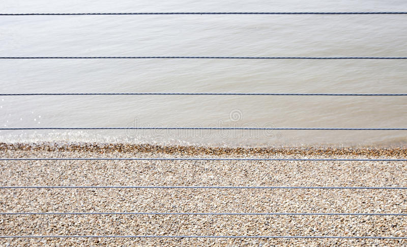 River Thames and Shingle beach behind wire rope fence royalty free stock photography