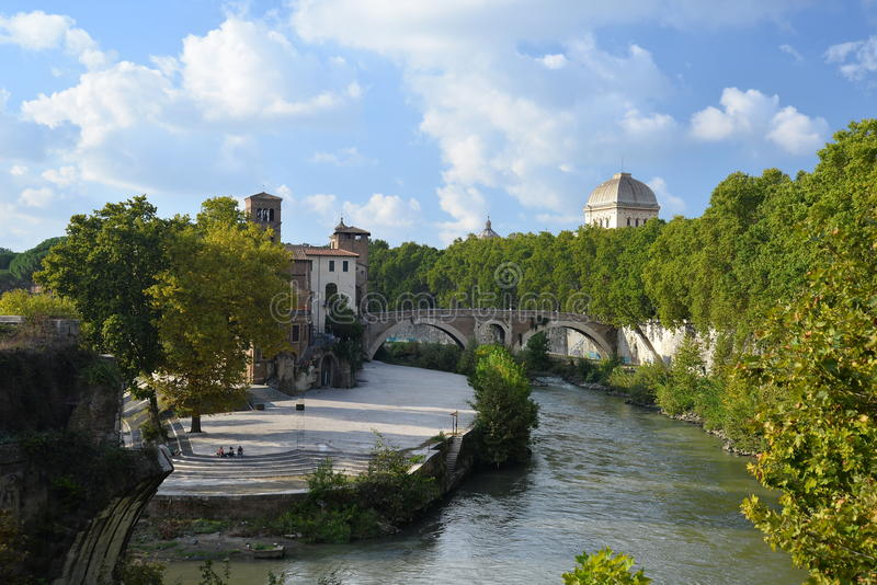 River Tiber and the Tiberina island in Rome, Italy. The Tiberina island and river Tiber - tevere - in Rome, Italy, view of the river embankment by sunny weather royalty free stock photos