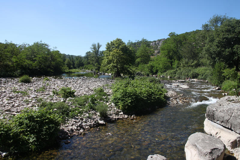 River tributary of the Ardeche in the south of France. Clear water and rapids with stony beach and rocks stock images