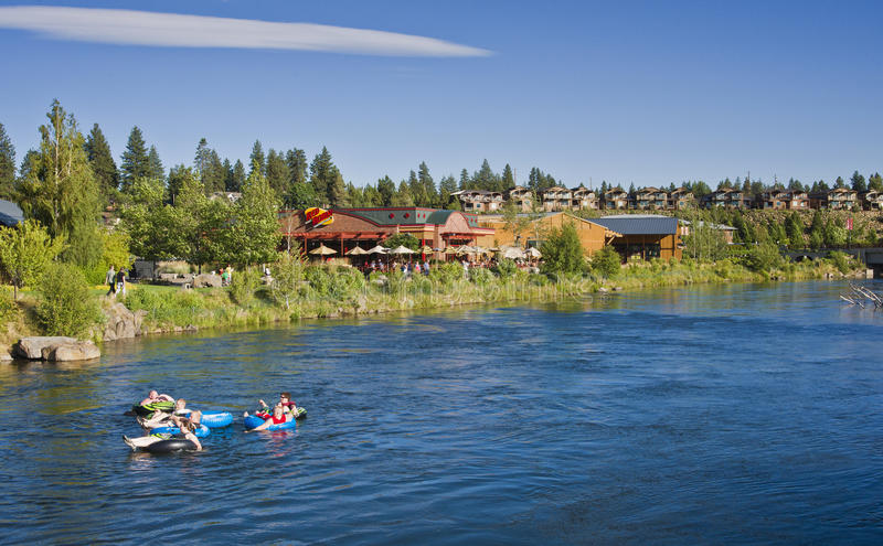 River Tubing, Bend, Oregon. Friends are having fun tubing down the Deschutes River in Bend, central Oregon. Bordered by a national forest and the Cascade royalty free stock images