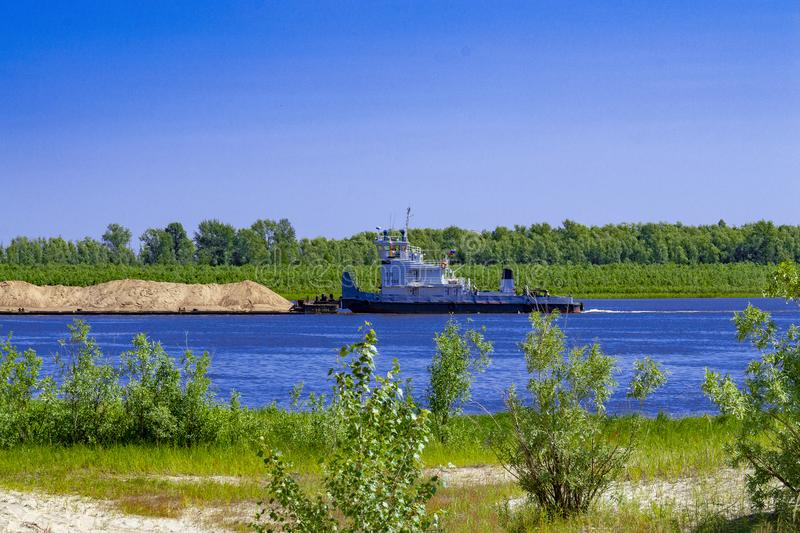 River.  A tugboat is floating along the river and pushing a barge with sand. Side view stock photography