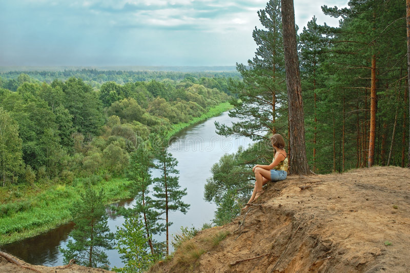River view. Young woman sitting and meditate on steep with peaceful river view royalty free stock images