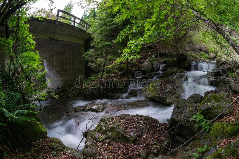 River with waterfalls under the bridge royalty free stock photo