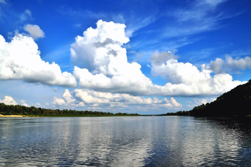 River and white clouds in the blue sky. Landscape royalty free stock images