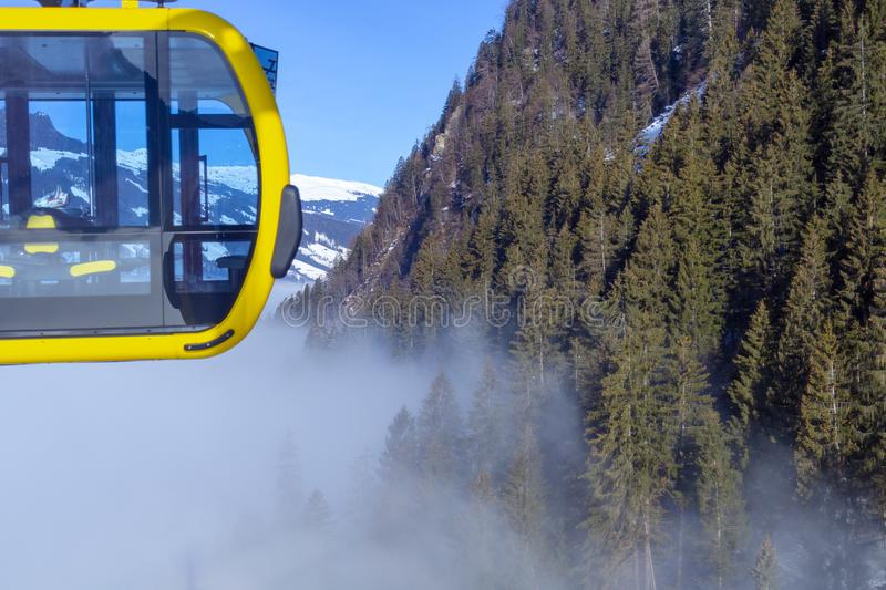 A river of white fog in the mountains and a ski lift in the foreground. Selective focus in the background.Alpine Alps mountain. A river of white fog in the stock photography