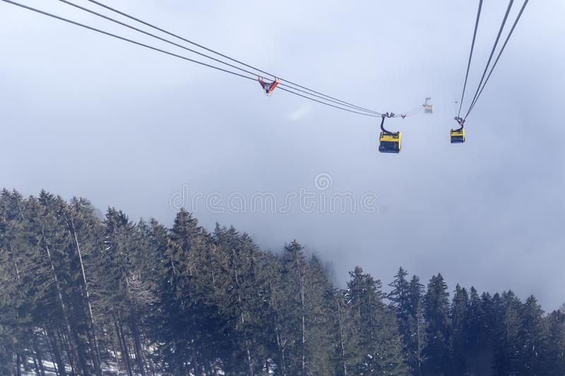A river of white fog in the mountains and a ski lift in the foreground. Selective focus in the background.Alpine Alps mountain. A river of white fog in the stock images