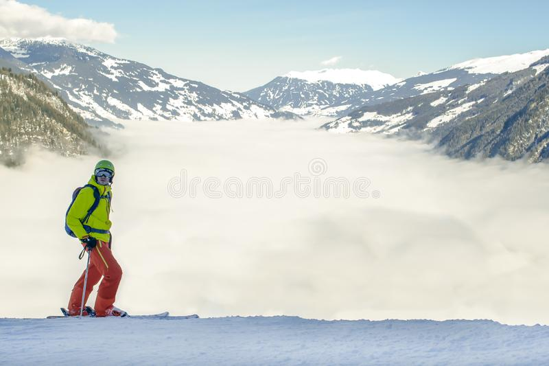 A river of white fog in the mountains and skier in front are preparing for the descent.Alpine Alps mountain landscape at Tirol,. A river of white fog in the stock image