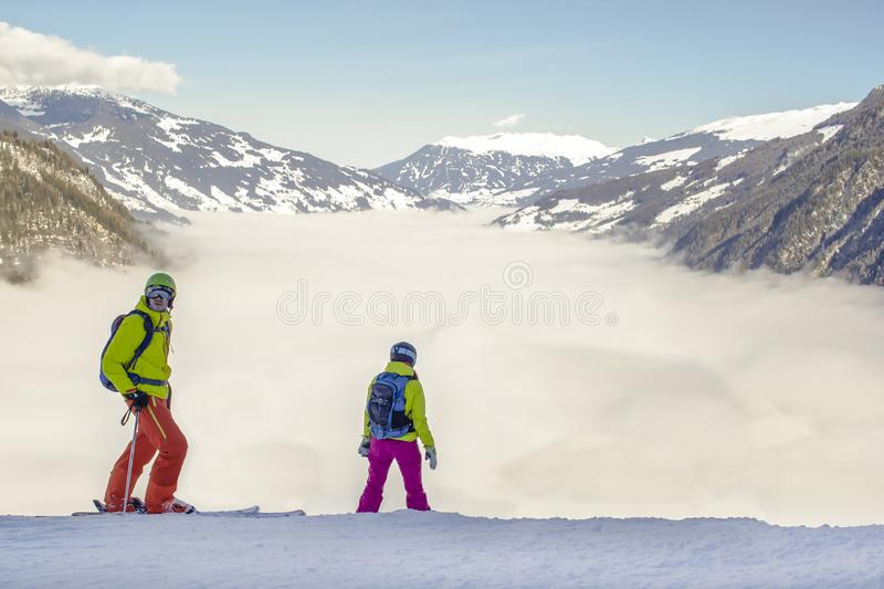 A river of white fog in the mountains and two people in front, snowboarders and skiers are preparing for the descent..Alpine Alps. Mountain landscape at Tirol royalty free stock image