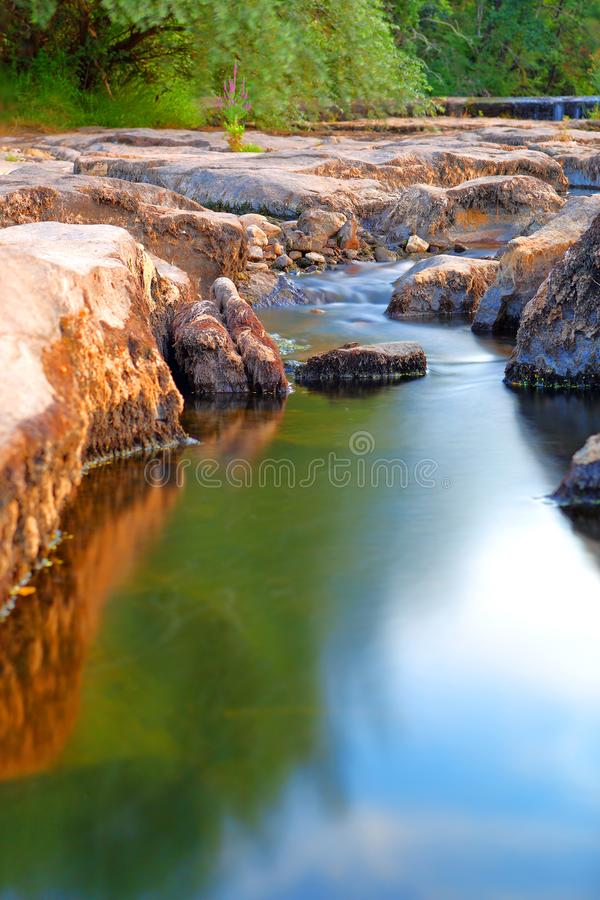 River winding among the rocks. Long exposure. Wipe effect. Provence river and reflection like a mirror : when trees , sky and water have an appointment stock photography