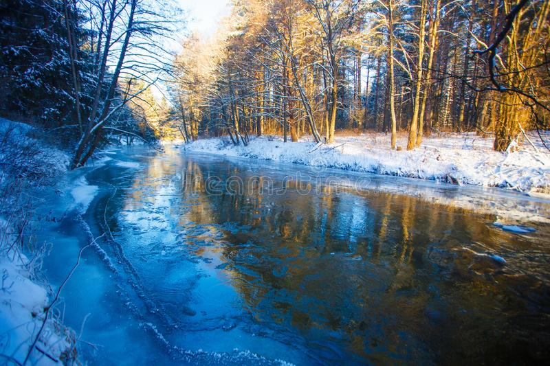 River in winter. Dappled sunlight streaming in mixed forest stock photography