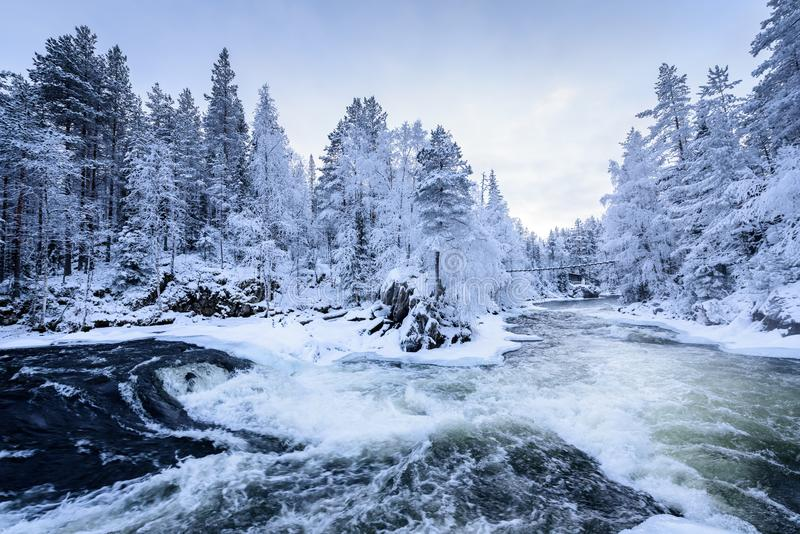 The river in winter season at Oulanka National Park, Finland. Background beautiful big blizzard blue bridge christmas cloudy clue cold covered day december stock photography