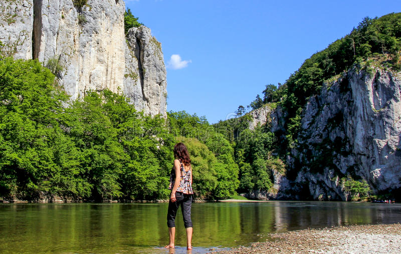 River and woman. Woman enters the river. Donau (Danube) in Weltenburg, Bavaria, Germany royalty free stock photography