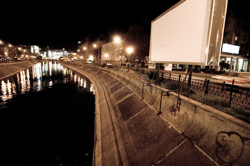 Riverbank. A picture of a riverbank at night. A blank giant advertisement billboard is on the banks. Picture in sepia stock photos