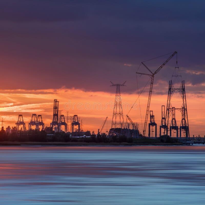Riverbank con las siluetas de las gr?as durante una puesta del sol, puerto de la terminal de contenedores de Amberes, B?lgica fotos de archivo