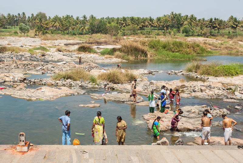 Riverbank i tłum kobiety i mężczyzna kąpać odzieżowego w wodzie i myjemy blisko Indiańskiej wioski zdjęcia royalty free