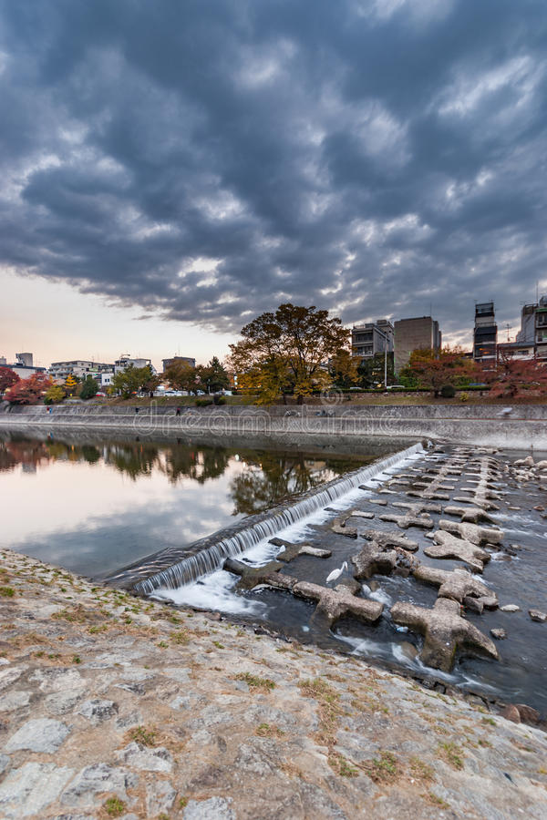 Riverbank of the Kamo-gawa river in Kyoto. On the riverbank of the Kamo-gawa river in Kyoto, Japan looking towards the east side of the river with dramatic stock photo