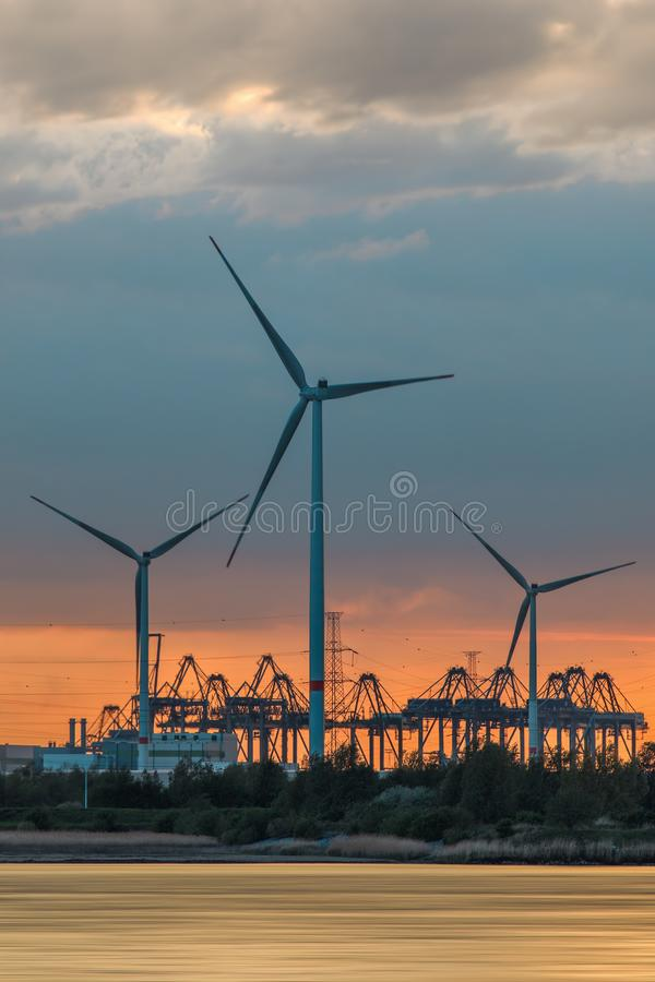 Riverbank with large windmills and silhouettes of container cranes during sunset, Port of Antwerp royalty free stock photography