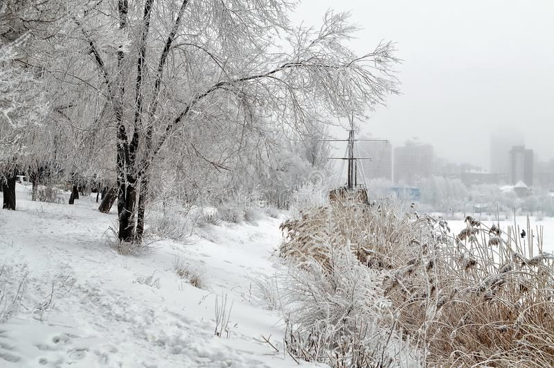 Riverbank, park, trees in the snow, ship, modern urban architecture royalty free stock photography