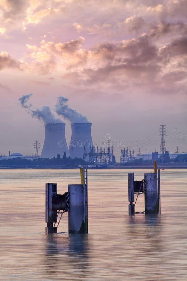 Riverbank z elektrowni? j?drow? Doel podczas zmierzchu z dramatycznymi cluds, port Antwerp zdjęcie stock
