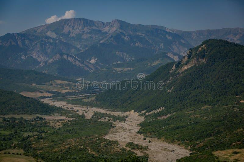 Riverbed między wzgórzami przerastającymi z drzewami i roślinnością na tle pasmo górskie zdjęcia stock