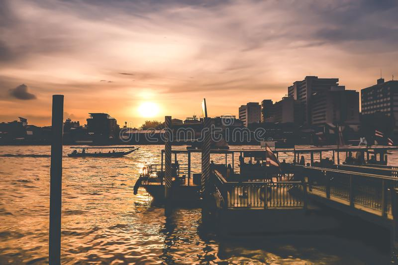RiverScape of Bangkok City and Chao Phraya River with Beautiful Sunset from Maharaj pier  in Bangkok City Thailand. Silhouette building and transportion travel stock photography