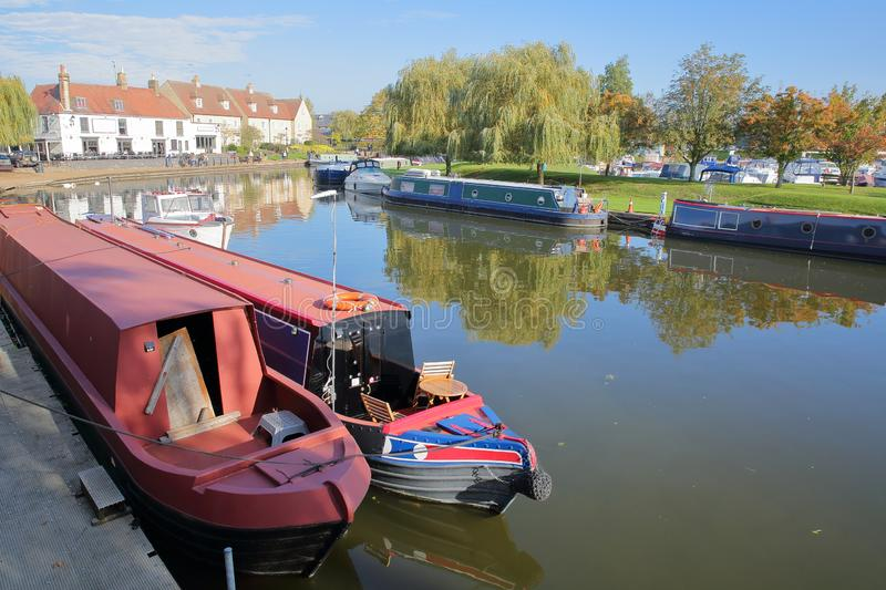 The riverside in Autumn with moored barges on the Great Ouse river and traditional houses, Ely, Cambridgeshire stock photo