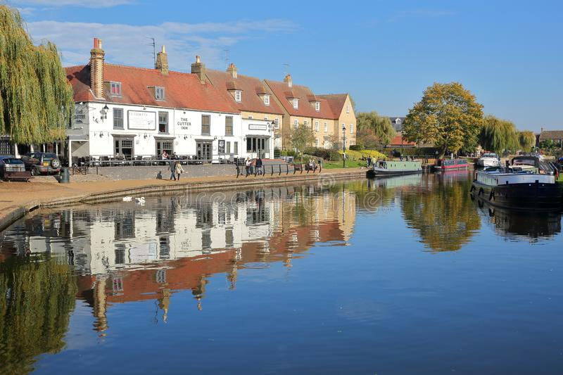 The riverside in Autumn with moored barges on the Great Ouse river and traditional houses royalty free stock image