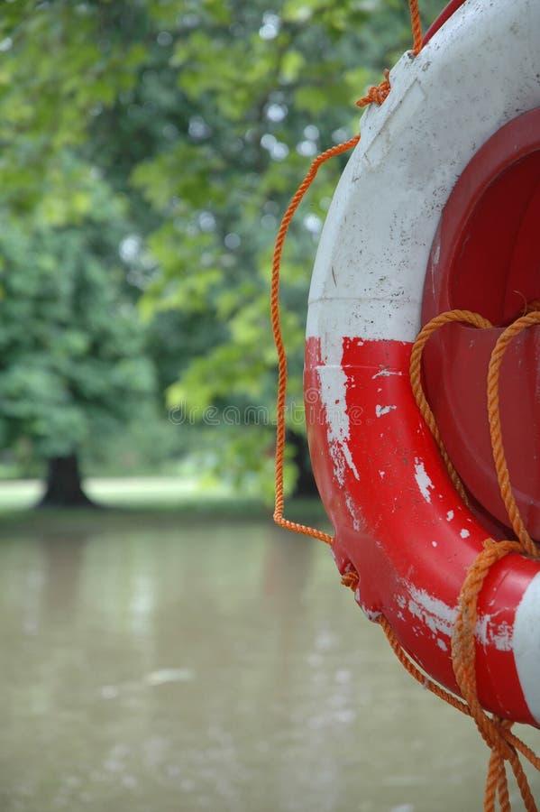 Riverside Lifebelt. A life saving lifebelt seen on the river bank stock image